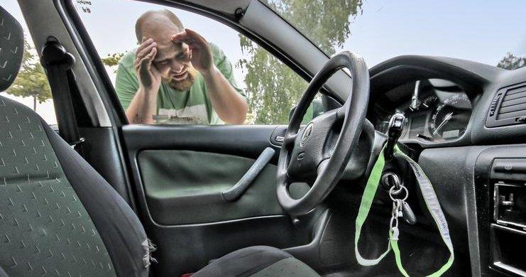 Kierowca patrzy na kluczyki zatrzaśnięte w aucie