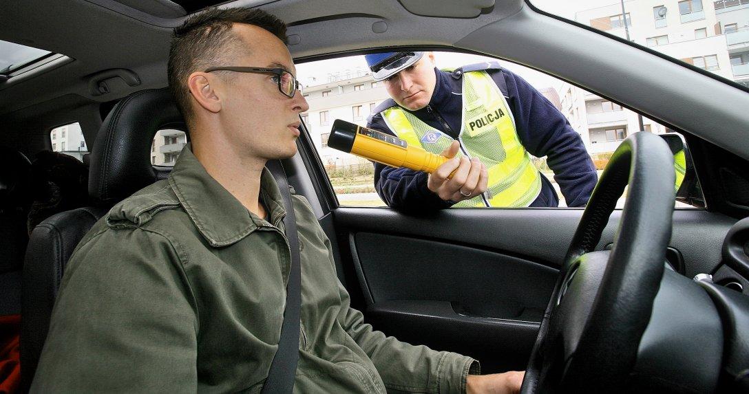 mężczyzna za kierownicą testowany przez policjanta alkomatem AlcoBlow