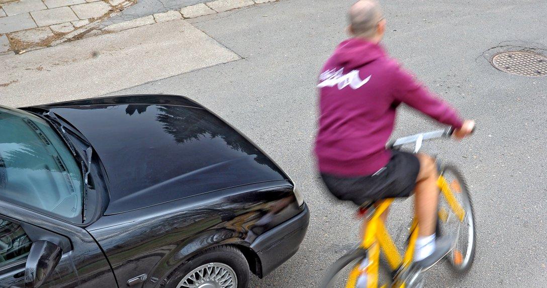 Rowerzysta przejeżdża przed samochodem