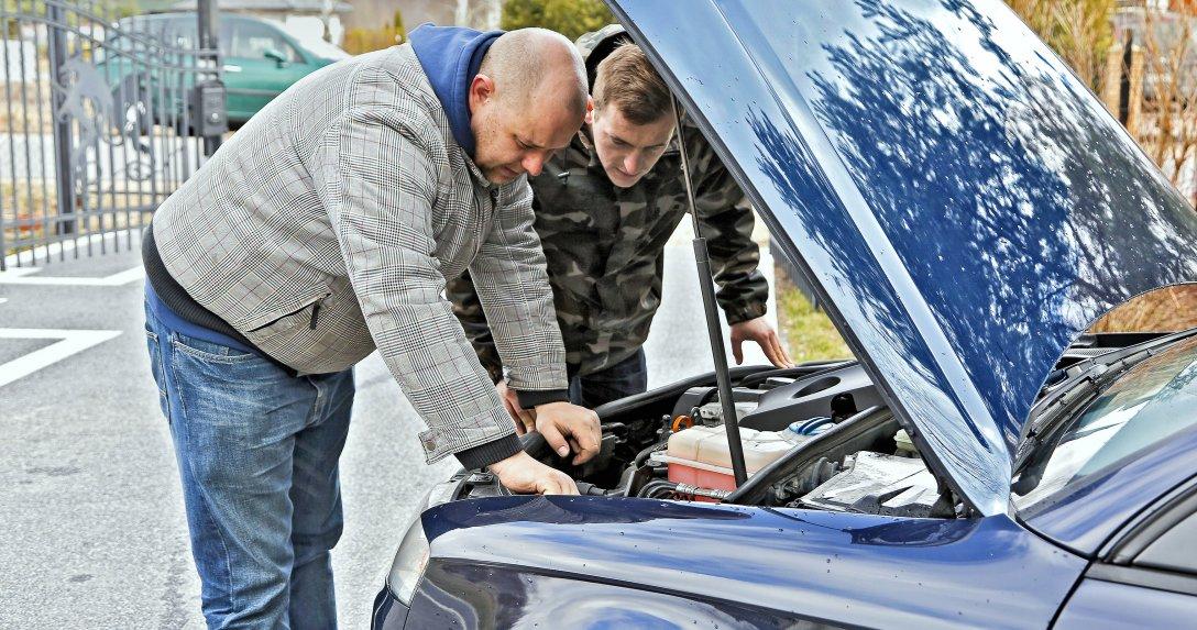Dwóch mężczyzn patrzy na silnik samochodu