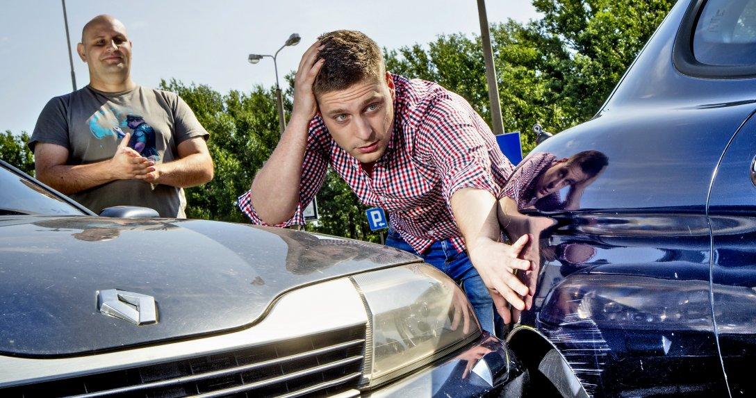 Dwóch mężczyzn patrzy na rozbite samochody