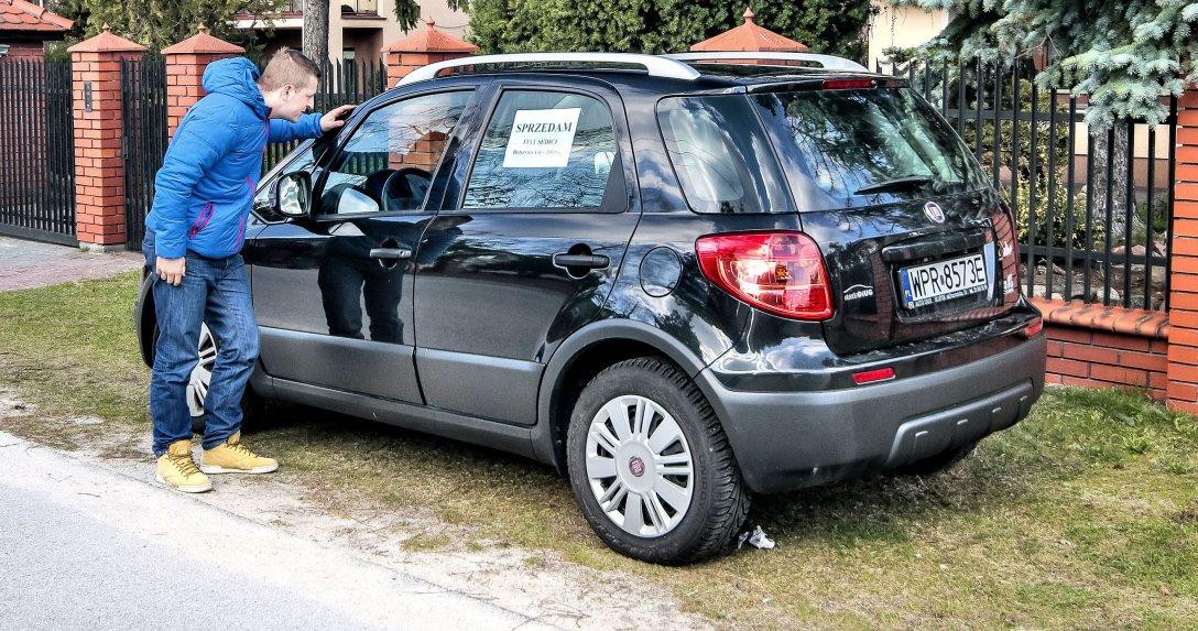 Mężczyzna ogląda używane auto wystawione na sprzedaż