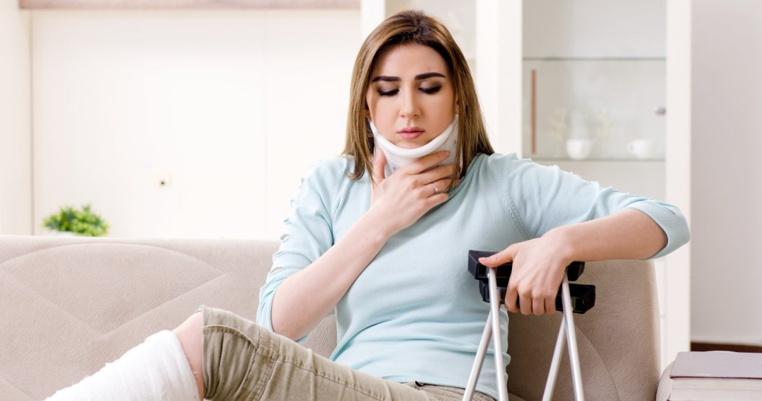kobieta w kołnierzu ortopedycznym, gipsie i z kulami w ręku siedząca na kanapie